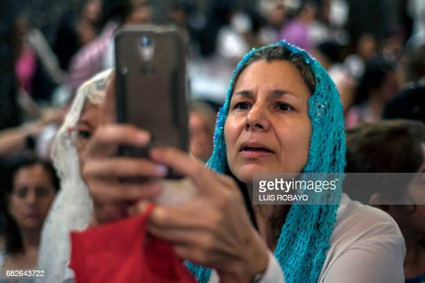 A pilgrim takes pictures with her mobile phone of a figure representing Our Lady of Fatima during the celebration of the centenary of her appearance...