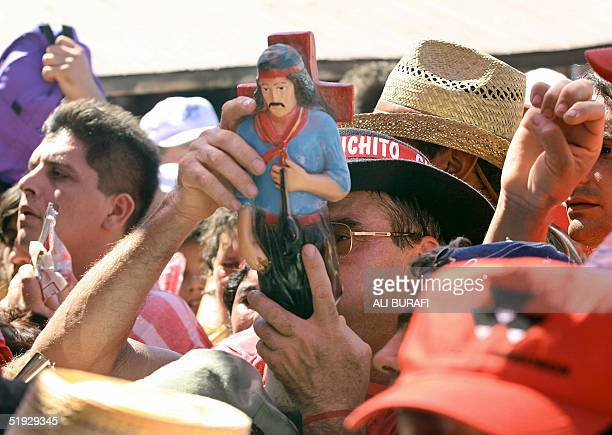 A pilgrim tries to get through the gates of the sanctury of Gauchito Gil with a figure of the venerated Saint near Mercedes in the Argentine province...