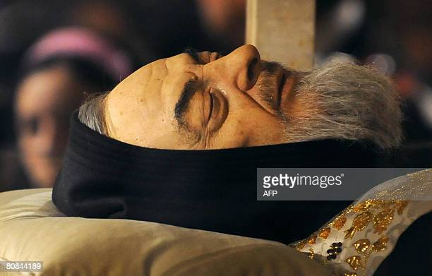 A pilgrim venerates the body of Padre Pio in a partglass coffin in the crypt of the old Church of St Mary of Grace at San Giovanni Rotondo in the...