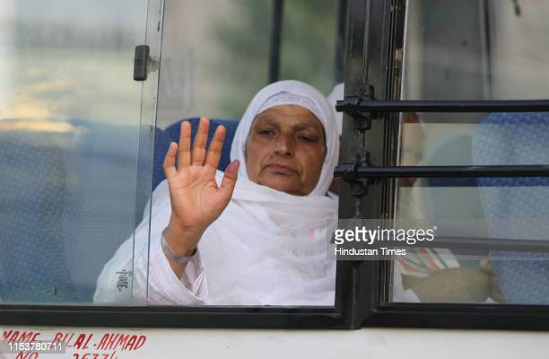 A pilgrim waves from a bus as she leaves for the annual Haj pilgrimage on July 4 2019 in Srinagar India The first batch of pilgrims from Jammu and...