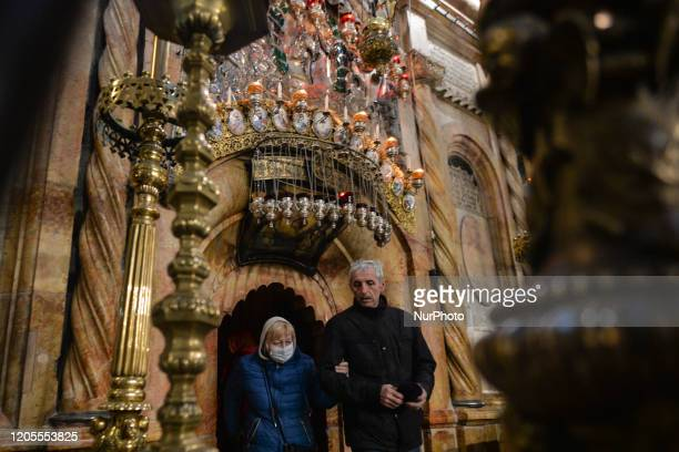A pilgrim wearing a protective mask seen inside the Church of the Holy Sepulchre in Jerusalem Old city 21 Israelis have so far tested positive for...