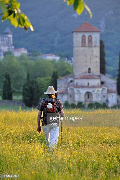 Pilgrim with a backpack and a pilgrim's staff walking in a field in bloom near the Basilica of Saint Just de Valcabrere SaintBertranddeComminges on...