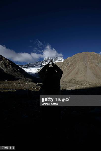 A pilgrim worships the snowcapped Kangrinboqe Mountain known as Mt Kailash in the West June 16 2007 in Purang County of Tibet Autonomous Region China...