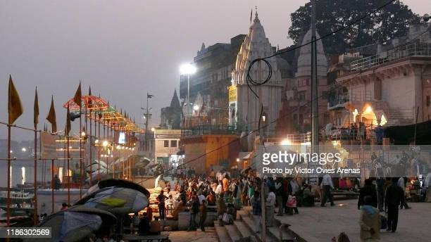 pilgrims and tourists at the mother ganga aarti religious ceremony in front of the ganges river at dusk in varanasi, uttar pradesh, india - victor ovies fotografías e imágenes de stock