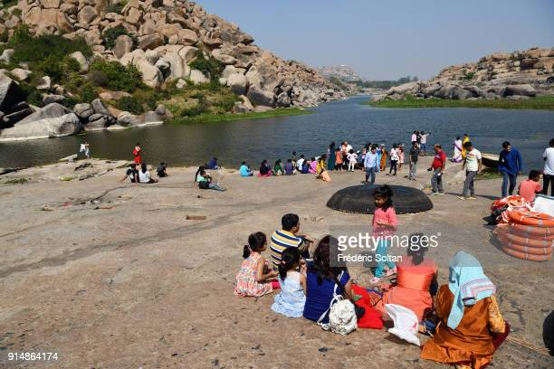 Pilgrims and tourists in the Tungabhadra River which is sacred in Hampi. Hampi is a village and a group of monuments, a UNESCO World Heritage Site...