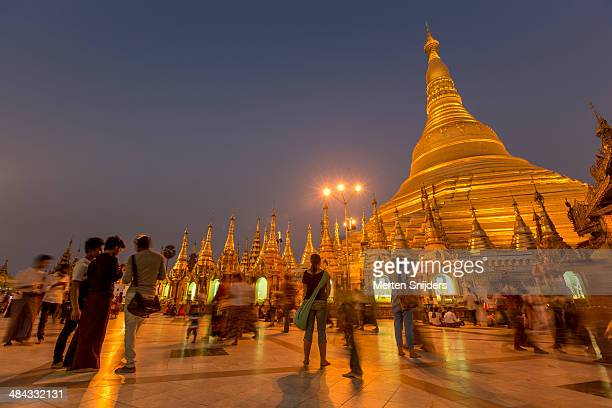 pilgrims and visitors of shwedagon after sunset - merten snijders stock pictures, royalty-free photos & images