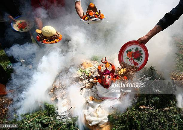 Pilgrims burn aromatic plants and offerings during a religious ritual to worship mountain gods at Siheji Village on July 14 2006 in Tongren County of...