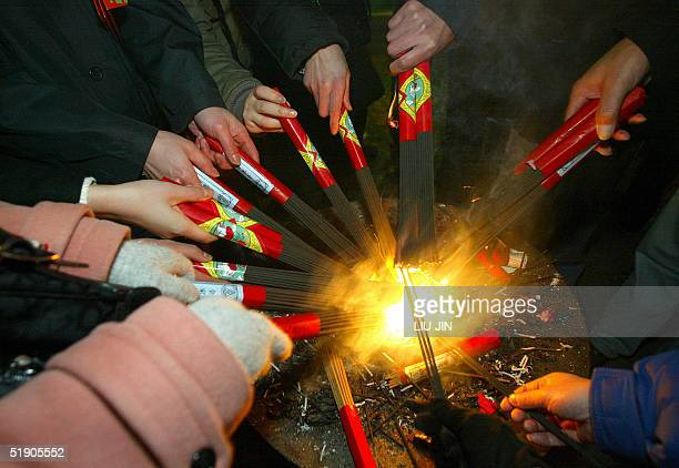 Pilgrims burn incense during the New Year's celebrations at Longhua Temple in Shanghai 01 January 2005 For Chinese when the new year comes ringing a...