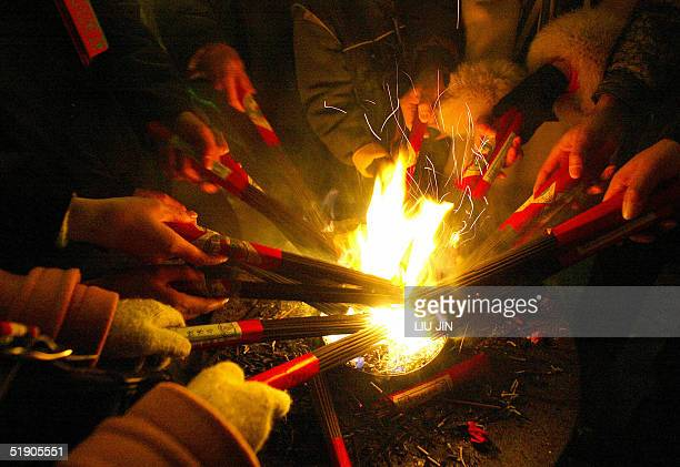 Pilgrims burn incense to pray and to make wishes during the New Year's celebrations at Longhua Temple in Shanghai 01 January 2005 For Chinese when...