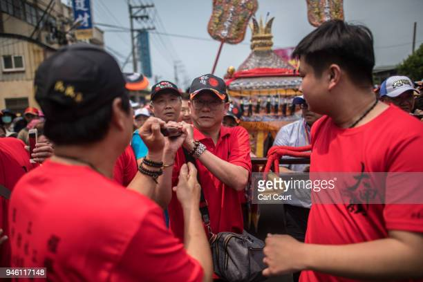 Pilgrims carry a sedan chair carrying a statue of the goddess Mazu as it is carried along on day 2 of the nine day Mazu pilgrimage on April 14 2018...