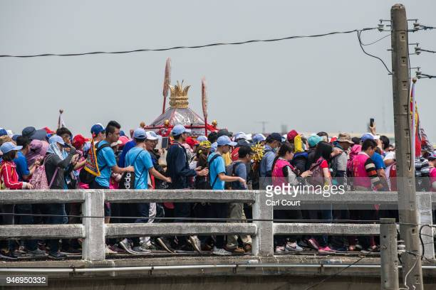 Pilgrims carry a statue of the goddess Mazu across a bridge as they approach Xingang Fengtian Temple where the statue will rest for two nights before...