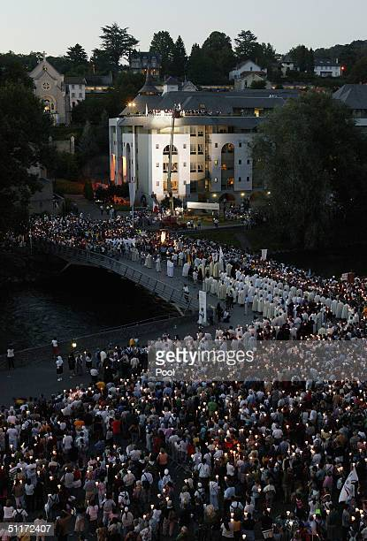 Pilgrims carry an statue of the Virgin Mary in a candlelit procession on August 14 2004 in Lourdes France Pope John Paul II arrived in Lourdes for a...