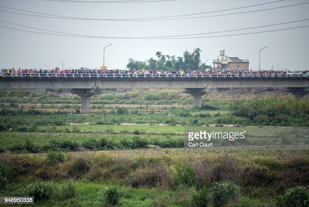 Pilgrims carrying a statue of the goddess Mazu pass over a bridge as they approach Xingang Fengtian Temple where the statue will rest for two nights...