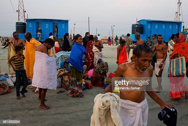 Pilgrims change clothes after bathing at Gangasagar Island due to shortage of temporaryt tents Every year thousands of Hindu pilgrims from all over...