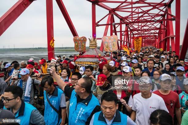 Pilgrims cross Xilou Bridge carrying a sedan chair holding a statue of the goddess Mazu on day three of the nine day Mazu pilgrimage on April 15 2018...