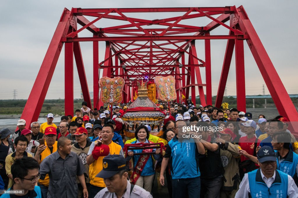 Pilgrims cross Xilou Bridge carrying a sedan chair holding a statue of the goddess Mazu on day three of the nine day Mazu pilgrimage on April 15, 2018 in Xilou, Taiwan. The annual Mazu Pilgrimage begins at Jenn Lann Temple in Taichung and sees around 200,000 pilgrims walk up to 12 hours each day for nine days carrying a statue of Chinese sea goddess Mazu in a sedan chair. The journey covers around 350 kilometres, much of it through mountainous and rugged terrain and visits more than 100 temples before returning to Taichung. The centuries-old pilgrimage is now recognised by UNESCO as living heritage and with an estimated 5 million participants spread over the nine days, it is considered to be one of the greatest religious festivals in the world.