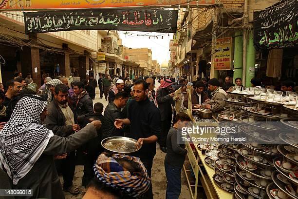 Pilgrims drink complimentary tea along Al-Rasool Street that leads to the main entrance to the Imam Ali Shrine on February 26, 2012 in Najaf, Iraq....