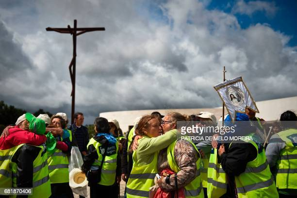 Pilgrims embrace each other upon their arrival at Fatima's Sanctuary central Portugal on May 11 2017 Two of the three child shepherds who reported...
