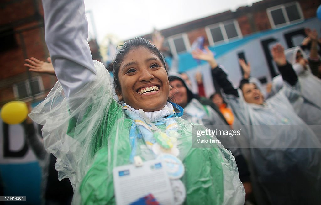 Pilgrims from Argentina celebrate as Pope Francis speaks in the Varghina favela, or shantytown, on July 25, 2013 in Rio de Janeiro, Brazil. More than 1.5 million pilgrims are expected to join Pope Francis for his visit to the Catholic Church's World Youth Day celebrations. Pope Francis will deliver his welcome address to the celebrations on Copacabana Beach later today as World Youth Day runs July 23-28.