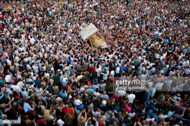 Pilgrims gather around a statue of the Virgin Mary being paraded during a procession in the village of El Rocio southern Spain on May 21 2018 El...