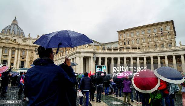 Pilgrims gather under umbrellas as Pope Francis delivers his message to them in St Peter's Square at The Vatican on November 1 during his Angelus...