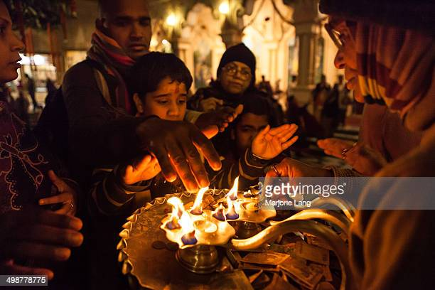 CONTENT] Pilgrims getting blessings from the holy fire during the evening darshan inside the Sri Krishna Balaram temple also called ISKCON temple of...
