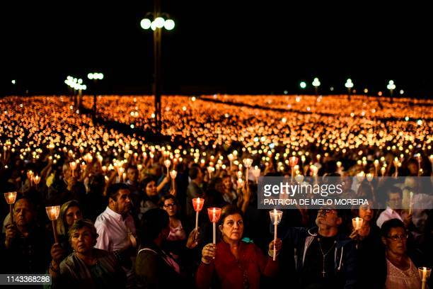 TOPSHOT Pilgrims hold candles as they pray during the candle procession at the Fatima shrine in Fatima central Portugal on May 12 2019 Thousands of...