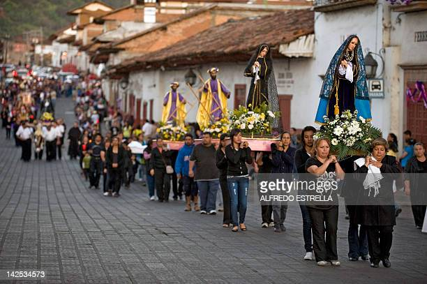 Pilgrims hold religious images during a peregrination at Patzcuaro municipality Michoacan Mexico during Good Friday on April 6 2012 Christians...