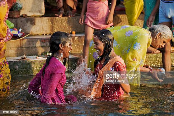 Pilgrims in colorful attire at the ghats in Varanasi. They flock to the Ganges river to perform puja, a religious ritual. They bring offerings to Mother Ganges and believe that the holy water cleanse them from all sins. India.
