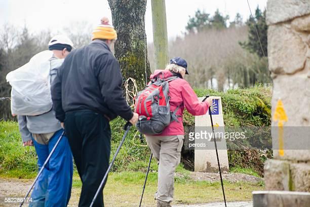 Pilgrims in the 'camino de Santiago', yellow arrow sign.