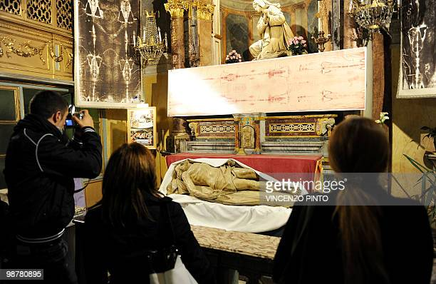 Pilgrims look at a Shroud reproduction and a Christ staute exposed in the San Lorenzo church in central Turin on May 1 2010 Pope Benedict XVI will...