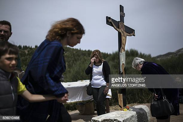 Pilgrims of the Greek Orthodox Church stand in front of an image of Jesus crucified during the ceremony marking the Apokathelosis, the removal of...