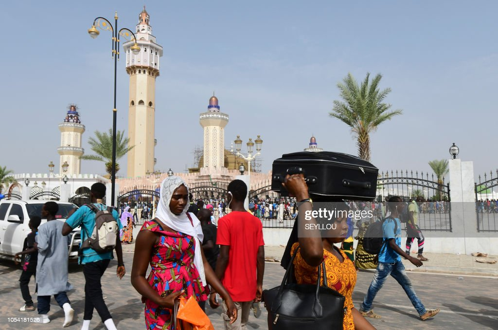 Pilgrims of the Mouride Brotherhood, a Sufi order, walk past the