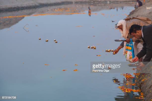 Pilgrims offering floating flowers and burning candles to the water in Vrindavan, India