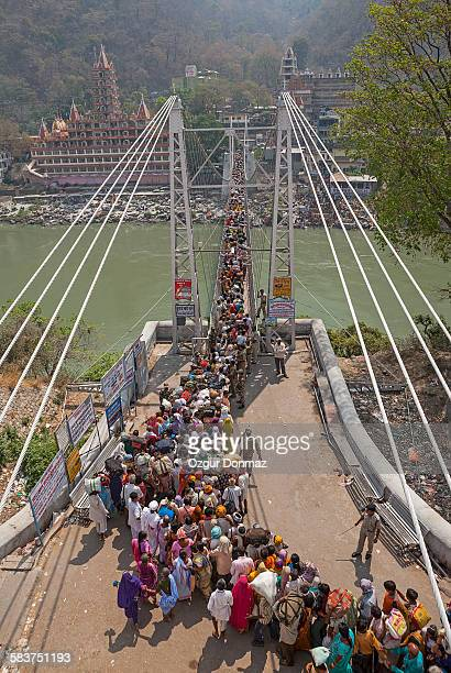 pilgrims passing the laksman jhula bridge, india - haridwar stock pictures, royalty-free photos & images