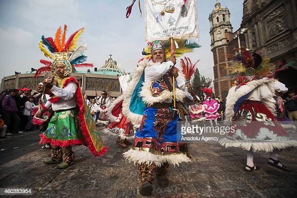 Pilgrims perform a traditional dance outside the Basilica of Guadalupe on Our Lady of Guadalupe's feast day in Mexico City Mexico on December 12 2014