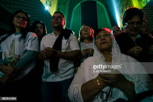 Pilgrims pray during the celebration of the centenary of the appearance of Our Lady of Fatima in Portugal on May 13 in Cali Colombia Two of the three...