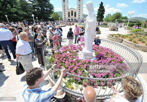 Pilgrims pray near a statue of the Virgin Mary in front of a Catholic church in SouthernBosnian town of Medjugorje on June 25 2010 It is belived that...