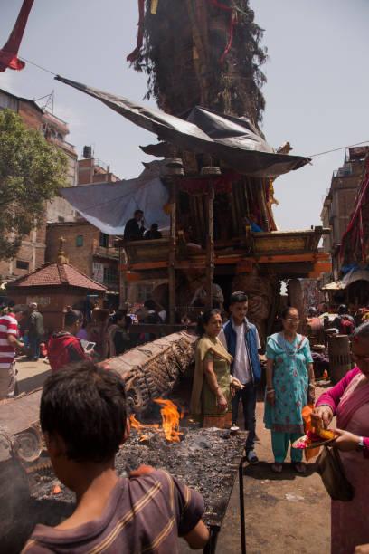 Pilgrims preparing offerings and lighting butter lamps at the base of an ornate chariot celebrating the Bunga Dyo Jatra Festival in Patan, Kathmandu, Nepal.