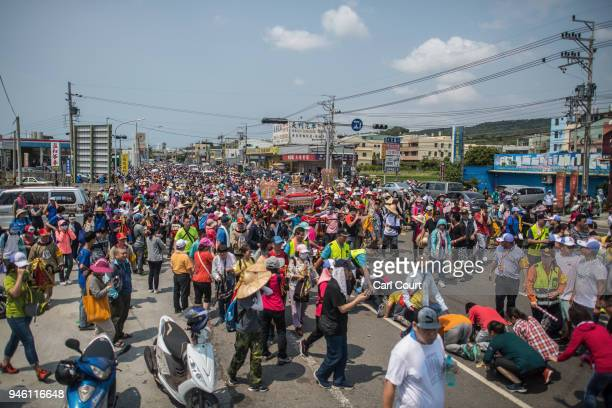 Pilgrims prostrate themselves as others walk alongside the sedan chair carrying a statue of the goddess Mazu on day two of the nine day Mazu...