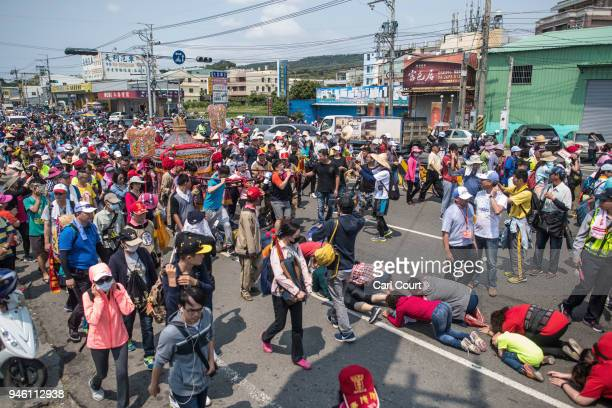 Pilgrims prostrate themselves beneath a sedan chair carrying a statue of the goddess Mazu as it is carried along on day two of the nine day Mazu...