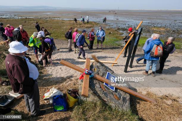 Pilgrims reach the end of their pilgrimage after celebrating Easter by carrying wooden crosses over the tidal causeway to Lindisfarne during the...