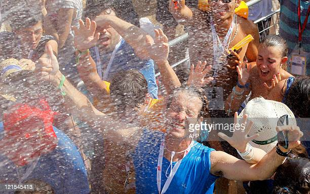 Pilgrims react as water is poured to refresh them as they gather in blistering heat on a vast dusty esplanade outside Madrid to hear a prayer vigil...