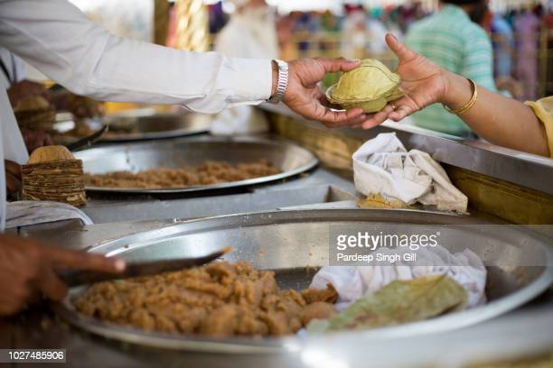 pilgrims receive karah-prasad (holy offering) at the golden temple (also known as sri harmandir sahib gurdwara) during the vaisakhi festival in amritsar, punjab, india - amritsar stock pictures, royalty-free photos & images