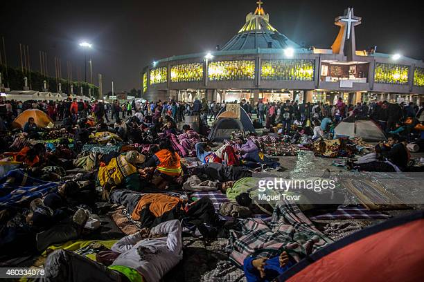 Pilgrims rest outside the Basilica of Guadalupe on December 11 2014 in Mexico City Mexico The Mexican tradition narrates the apparitions of the...