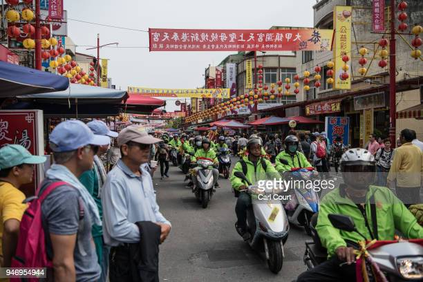 Pilgrims ride motorcycles along a street near Xingang Fengtian Temple where the statue of Mazu will rest for two nights before resuming its journey...