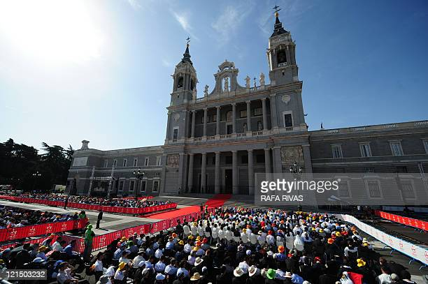 Pilgrims sat outside at the Almudena Cathedral attend a mass celebrated by Pope Benedict XVIduring the World Youth Day festivities in Madrid on...