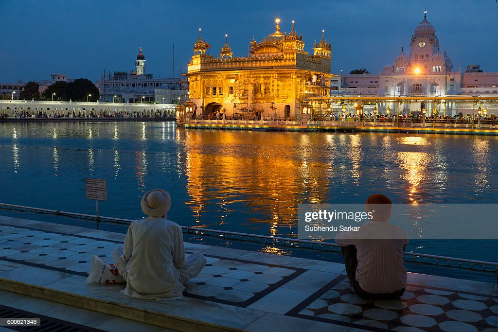 Pilgrims sit in front of the Golden Temple after dark Sri Harmandir Sahib or Sri Darbar Sahib or the `Golden Temple` is the holiest temple of Sikhism