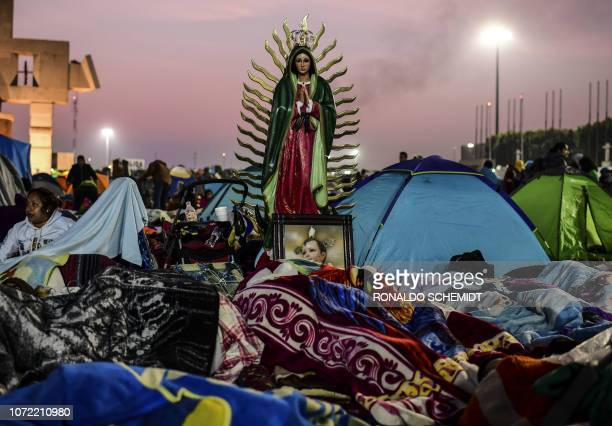 TOPSHOT Pilgrims sleep near an image of the Virgin of Guadalupe during the annual celebrations at the Basilica of Guadalupe in Mexico City on...