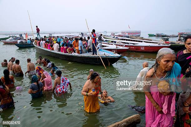 Pilgrims take bath in the waters of the river Ganges while others ride boat in Varanasi Varanasi is a holy town for the Hindus where numerous...